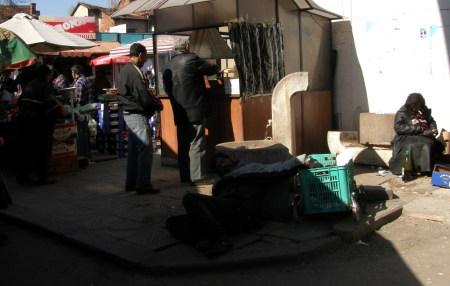 пиян човек дреме до една чешма, полегнал на земята, на пазара Красно село, София