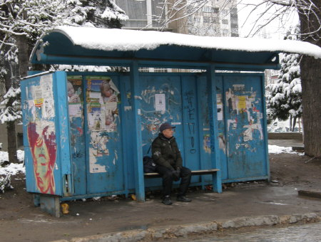 възрастен мъж с торбичка чака приседнал на спирка, цялата нашарена с надписи, сняг, София