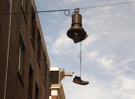 висящи на въже-лапма на улицата маратонки в Амстердам